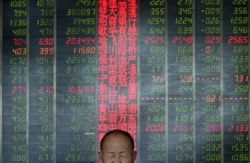 An investor reacts in front of an electronic board showing stock information at a brokerage house in Taiyuan