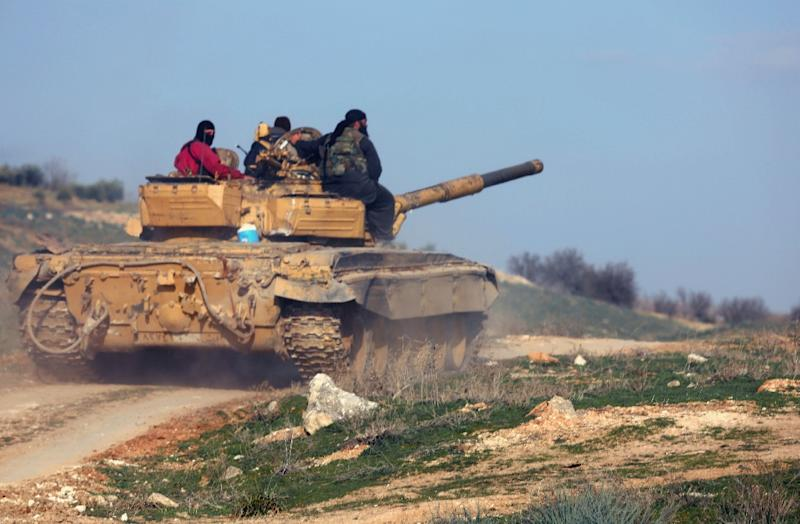 Rebel fighters sit on top of a tank as they head to the front line of battles against Syrian pro-government forces, near the city of Hama, on February 18, 2014