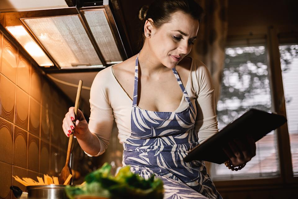 Cheerful young woman wearing an apron watching internet tutorial and cooking spaghetti in the kitchen at home