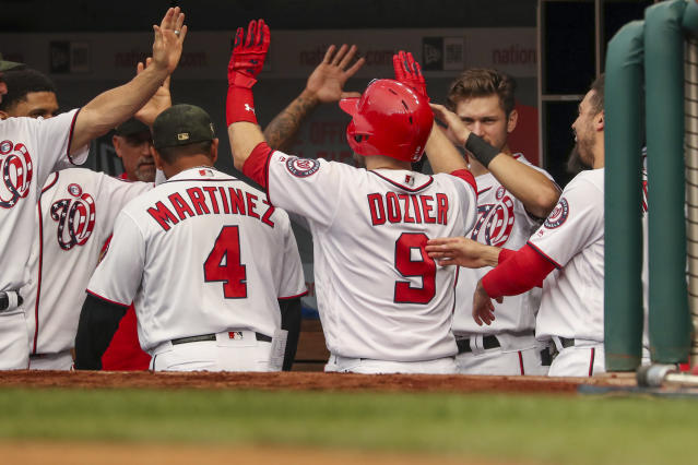 Washington Nationals' Brian Dozier (9) high-fives teammates after hitting a solo home run during the second inning of the team's baseball game against the Chicago Cubs, Saturday, May 18, 2019, in Washington. (AP Photo/Andrew Harnik)