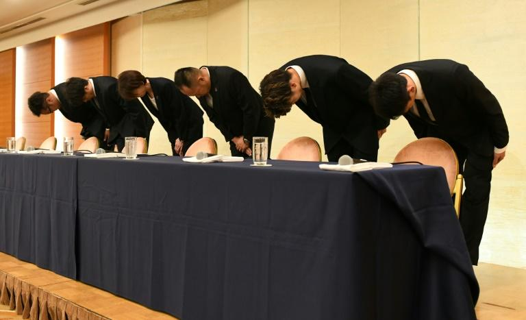 Four Japanese basketball players, seen here bowing during a press conference, were spotted in a red light area wearing team jerseys