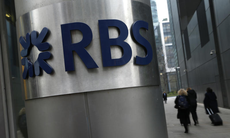FILE - In this Thursday, Jan. 26, 2017 file photo, people walk past one of the headquarter buildings showing the logo of the Royal Bank of Scotland in London. The British government has sold a 7.7 percent stake in Royal Bank of Scotland, taking a tentative step toward returning the bank to private ownership almost a decade after it was bailed out at the height of the financial crisis. (AP Photo/Alastair Grant/File)
