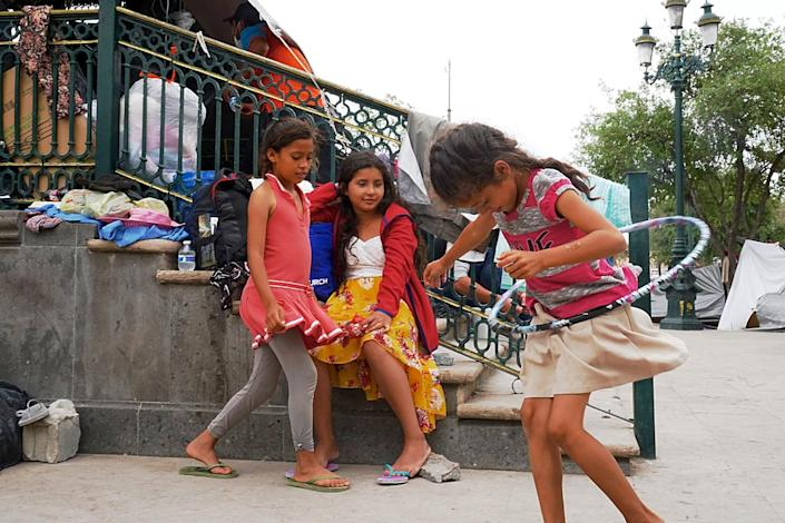 Girls play or sit on steps nearby
