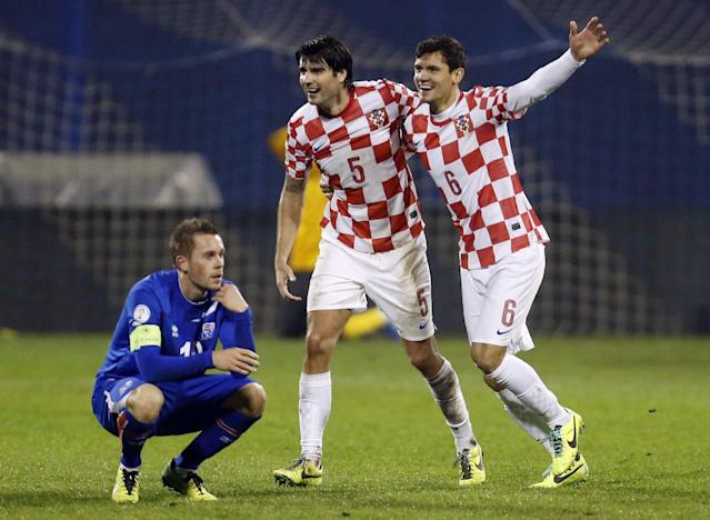 Croatia's Vedran Corluka, center and Dejan Lovren celebrate their victory over Iceland as Iceland's Gylfi Sigurosson looks on during their World Cup qualifying playoff second leg soccer match in Zagreb, Croatia, Tuesday, Nov. 19, 2013. (AP Photo/Darko Bandic)
