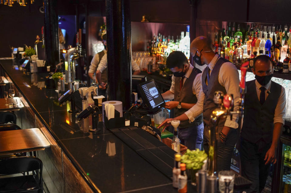 """Members of staff at The Piano Works club in Farringdon, London, Friday, July 16, 2021, prepare for its reopening as part of the relaxation of COVID-19 restrictions. Thousands of young people plan to dance the night away at """"Freedom Day"""" parties as the clock strikes midnight Monday, when almost all coronavirus restrictions in England are due to be scrapped. Nightclubs can open fully and are not required to use vaccine passports. (AP Photo/Alberto Pezzali)"""