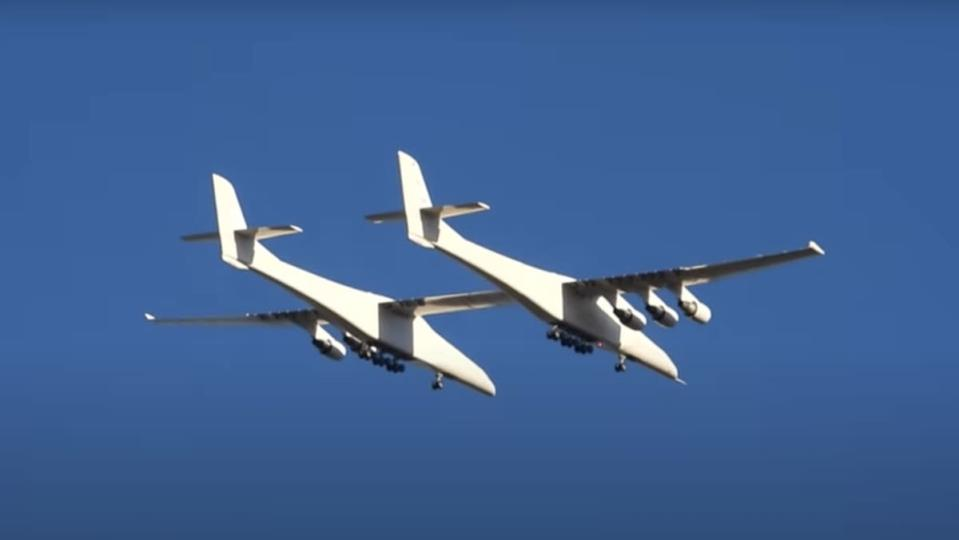 The Roc, the world's largest plane, which looks like a biplane with six engines, flying against a blue sky