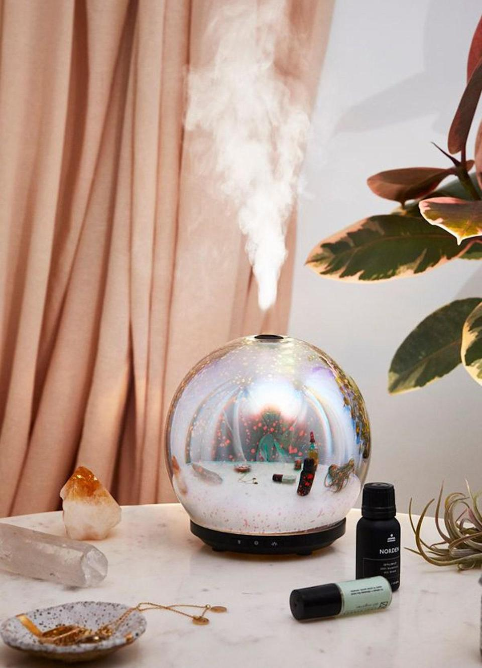 """For a mystical vibe, this holographic orb has a range of LED light settings to compliment the aromatic puffs. $65, Urban Outfitters. <a href=""""https://www.urbanoutfitters.com/shop/3d-led-gala-essential-oil-diffuser?category=PRODUCTTRAY&color=095"""" rel=""""nofollow noopener"""" target=""""_blank"""" data-ylk=""""slk:Get it now!"""" class=""""link rapid-noclick-resp"""">Get it now!</a>"""