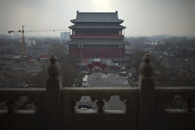 "In this Jan. 15, 2013 photo, seen from the Bell Tower, a crane works on a construction site near the Drum Tower among ""hutong"" courtyard homes in central Beijing, China. The district government wants to demolish these dwellings, move their occupants to bigger apartments farther from the city center and redevelop a square in 18th century Qing Dynasty fashion. (AP Photo/Alexander F. Yuan)"