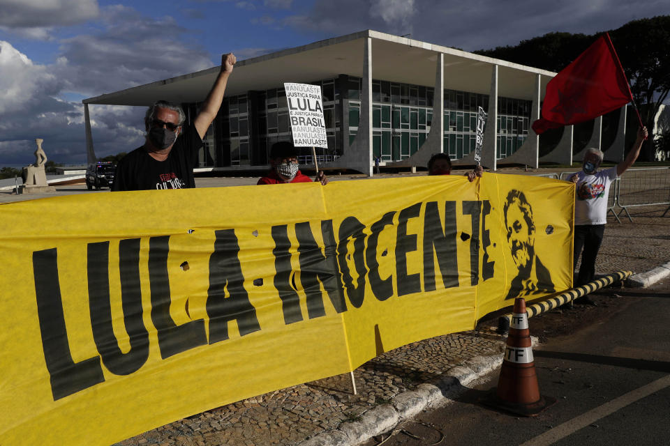 "Worker Party members chant, ""Lula Free,"" showing their support during a demonstration outside the Supreme Court while holding a banner featuring Brazil's former President Luiz Inacio Lula da Silva and a message that reads in Portuguese: ""Lula innocent,"" in Brasilia, Brazil, Tuesday, March 9, 2021. A top judge has thrown out both corruption convictions of the former president, opening the way for a possible battle against conservative incumbent Jair Bolsonaro in next year's elections. (AP Photo/Eraldo Peres)"