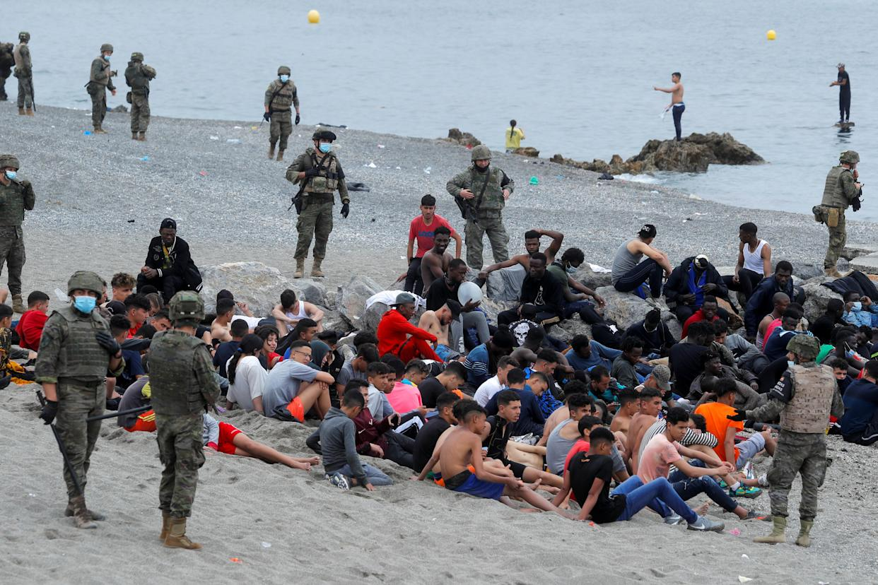 Spanish legionnaires stand around Moroccan citizens, after thousands of Moroccans swam across Spanish-Moroccan border on Monday. (Reuters)