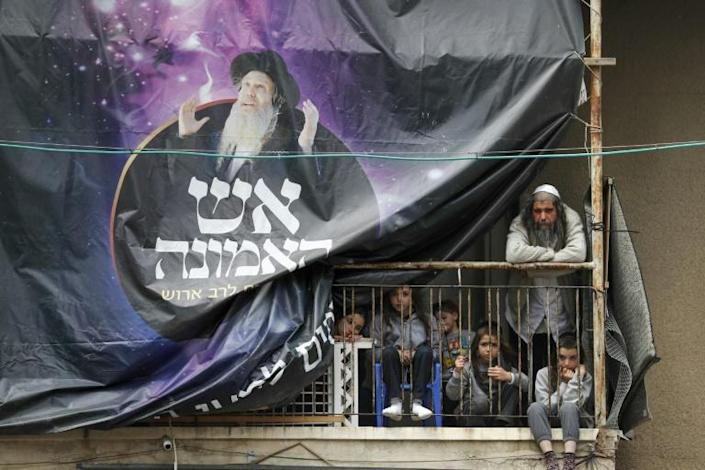 An ultra-Orthodox Jewish man and children watch from a balcony as Israeli security forces close a synagogue (AFP Photo/Ahmad GHARABLI)
