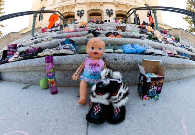 Hundreds of shoes and stuffed animals were left on the steps of the Saskatchewan legislature this weekend in honour of 215 children whose bodies were found in a mass grave in Kamploops B.C. earlier this week, on May 30, 2021 in Regina. (Bryan Eneas/CBC News  - image credit)