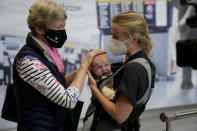 Susan Handfield, left, meets her baby granddaughter Charlotta for the first time, held by her mother Eva as they arrive from a Berlin flight at Terminal 5 of Heathrow Airport in London, Monday, Aug. 2, 2021. Travelers fully vaccinated against coronavirus from the United States and much of Europe were able to enter Britain without quarantining starting today, a move welcomed by Britain's ailing travel industry. (AP Photo/Matt Dunham)
