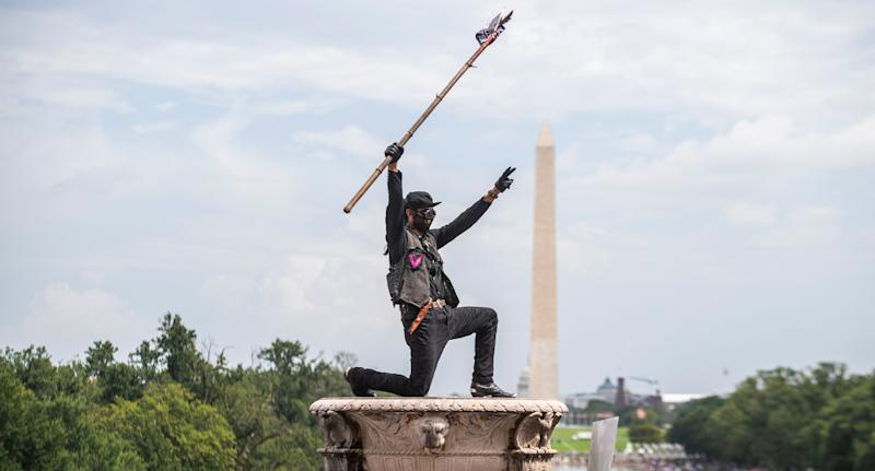 """A demonstrator is seen at the Lincoln Memorial during the """"Get Your Knee Off Our NecksÓ Commitment March. Source: AAP"""