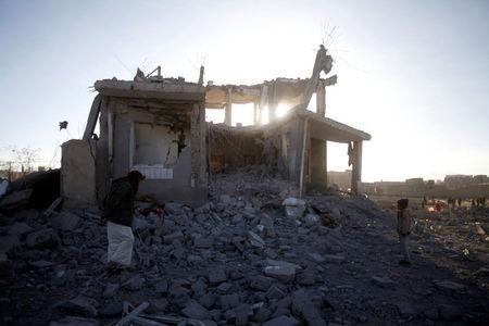 People inspect damage at the site of a Saudi-led air strike, north of Yemen's capital Sanaa