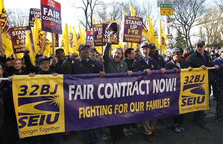 Hector Figueroa (center raising hat), president local chapter 32BJ of the Service Employees International Union (SEIU), leads a march in support of a new contract for apartment building workers in New York City, April 2, 2014. REUTERS/Mike Segar