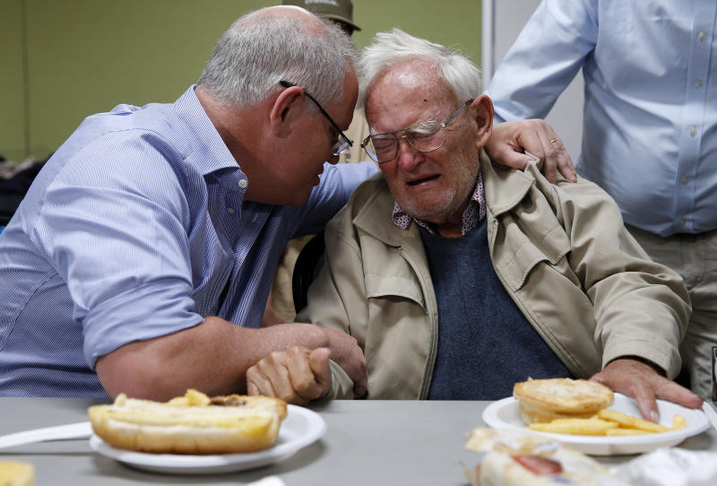 Prime Minister Scott Morrison comforts 85-year-old bushfire evacuee Owen Whalan of Half Chain road in Koorainghat at Club Taree Evacuation Centre in Taree, New South Wales on Sunday. Source: AAP