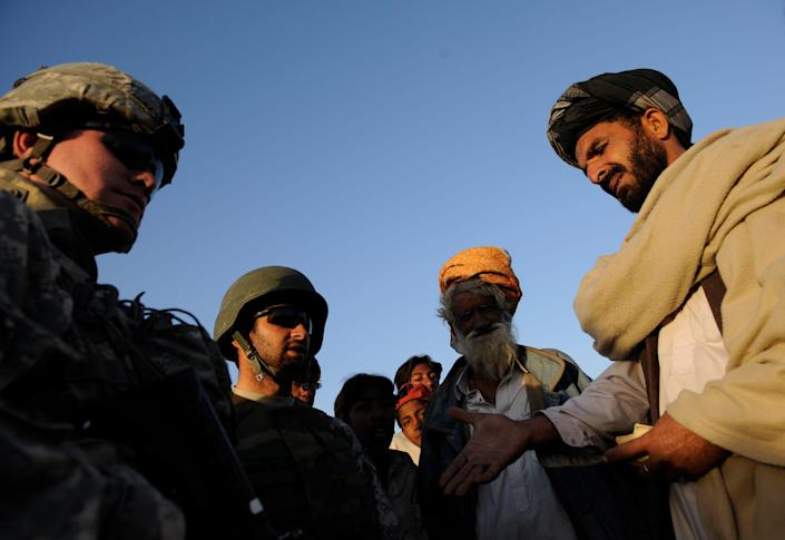 U.S. troops talk with villager through an interpreter in Terezayi, Afghanistan.