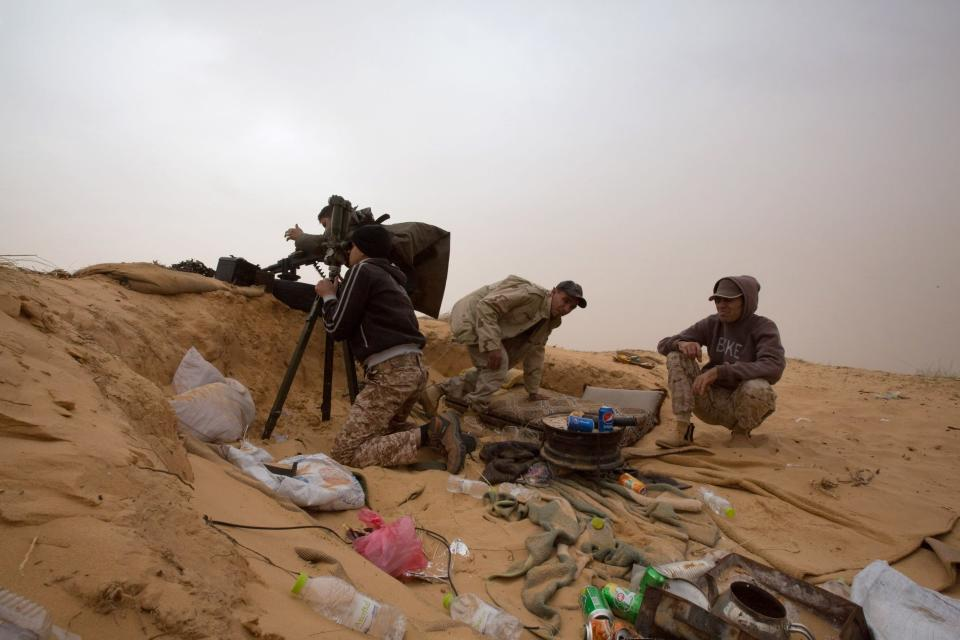 """FILE - In this Saturday, Feb. 21, 2015 file photo, Libyan soldiers aim their weapons during clashes with militants on the frontline in Al Ajaylat, 120 kilometers (75 miles) west of Tripoli, Libya. The United Nations said Friday, Oct. 23, 2020, that the two sides in Libyan military talks had reached a """"historic achievement"""" with a permanent cease-fire agreement across the war-torn North African country. (AP Photo/Mohamed Ben Khalifa, File)"""