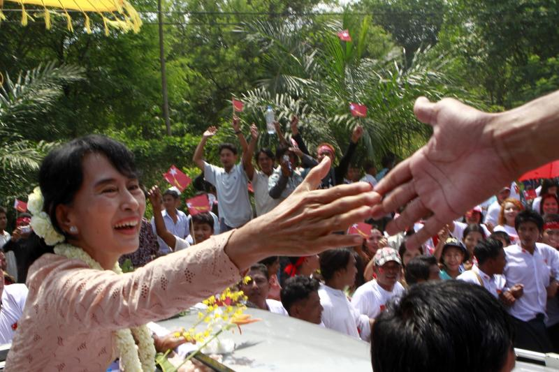 Nobel Peace Prize laureate Aung San Suu Kyi greets supporters from her vehicle during her election campaign trip to Myeik Archipelago, in the southern most part of Myanmar, Saturday, March 24, 2012. (AP Photo/Khin Maung Wiin)