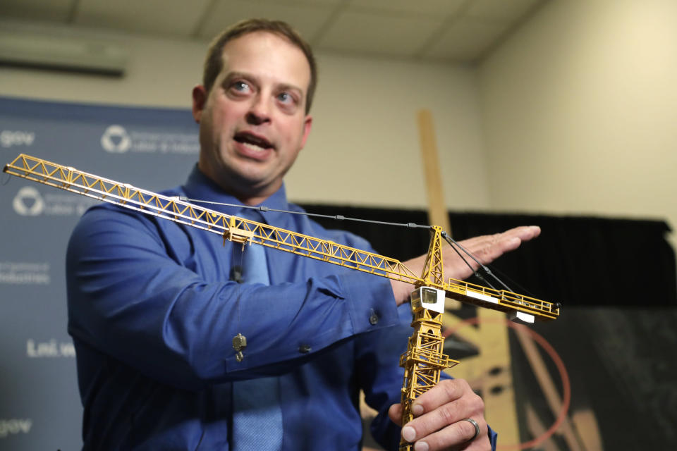 Brian Haight, crane program manager for Washington state's Department of Labor and Industries, uses a model of a crane during a news conference Thursday, Oct. 17, 2019, in Tukwila, Wash., to explain the collapse of a crane earlier in the year in Seattle that killed four. Washington State's L&I released the results of its investigation on the collapse Thursday. It found, as experts have long suspected, that the crane toppled because workers who were disassembling it had prematurely removed pins securing the sections of the crane's mast. (AP Photo/Elaine Thompson)