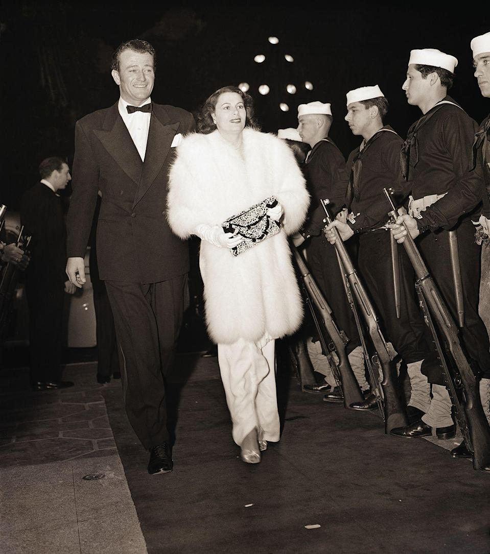 <p>John Wayne and his wife Josephine walk down the carpet at the Hollywood premiere of <em>Reap the Wild Wind</em> in 1942.</p>