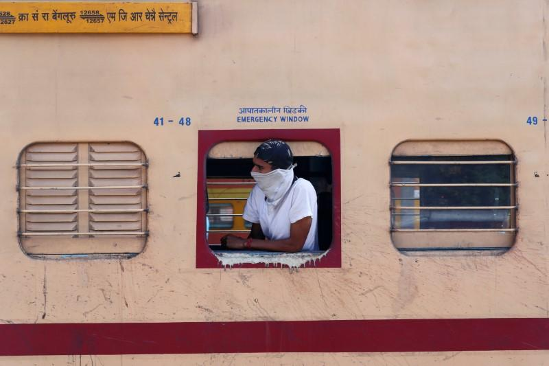 A man with his face covered looks out from a train during lockdown by the authorities to limit the spreading of coronavirus disease (COVID-19), in New Delhi