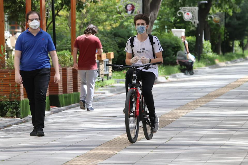 KIRKLARELI, TURKEY - MAY 15: A young rides a bike at Istasyon Street after youths between 15-20 years across Turkey allowed to leave their homes, remaining within walking distance and wearing masks, in Kirklareli, Turkey on May 15, 2020. Turkey on Friday eased coronavirus (Covid-19) restrictions for young people between 15- 20 years old. (Photo by Ozgun Tiran/Anadolu Agency via Getty Images)