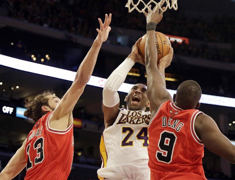 Los Angeles Lakers guard Kobe Bryant (24) shoots as he is defended by Chicago Bulls center Joakim Noah and forward Luol Deng (9), of Sudan, in the first half of an NBA basketball game in Los Angeles Sunday, March 10, 2013. (AP Photo/Reed Saxon)