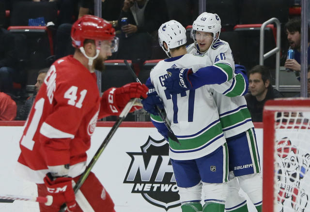 Vancouver Canucks center Elias Pettersson (40), of Sweden, celebrates his first period goal with right wing Nikolay Goldobin (77), of Russia, as Detroit Red Wings center Luke Glendening (41) skates away during an NHL hockey game Tuesday, Nov. 6, 2018, in Detroit. (AP Photo/Duane Burleson)