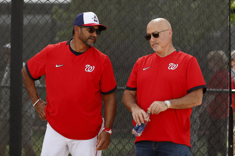 Washington Nationals manager Dave Martinez, left, talks with general manager Mike Rizzo during spring training baseball practice Monday, Feb. 17, 2020, in West Palm Beach, Fla. (AP Photo/Jeff Roberson)