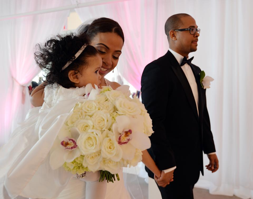 Bride Veronica Vizcaino holding daughter Olivia and groom Gustavo Espinal after they are married on the 58th floor of the Empire State Building. (Photo: STAN HONDA/AFP via Getty Images)