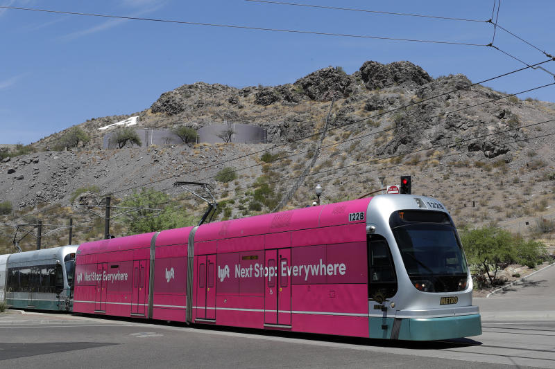 "FILE - In this Monday, Aug. 26, 2019, file photo, a light rail train runs through downtown Tempe, Ariz. Phoenix voters said ""yes"" to expanding light rail transportation in the nation's fifth largest city Tuesday by soundly saying ""no"" to a measure that aimed to stop any more development of the system, according to early, unofficial returns. (AP Photo/Matt York, File)"
