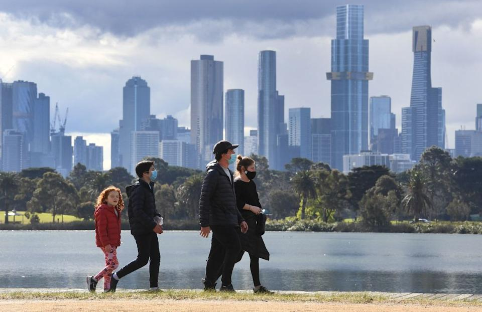 People exercise in front the city skyline in Melbourne.
