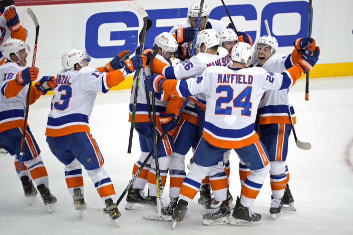 The New York Islanders celebrate a winning overtime goal by Kyle Palmieri in Game 1 of an NHL hockey Stanley Cup first-round playoff series against the Pittsburgh Penguins in Pittsburgh, Sunday, May 16, 2021. (AP Photo/Gene J. Puskar)