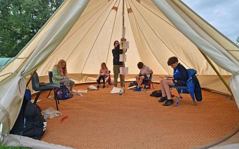 Teacher Holly Haime teaches year five pupils arts and crafts as they make paper aeroplanes inside a teepee style tent at Llanishen Fach Primary School in Cardiff - PA