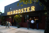 People arrive at the Red Rooster restaurant owned by celebrity chef Marcus Samuelsson, Wednesday, April 14, 2021, in the Overtown neighborhood in Miami. (AP Photo/Lynne Sladky)