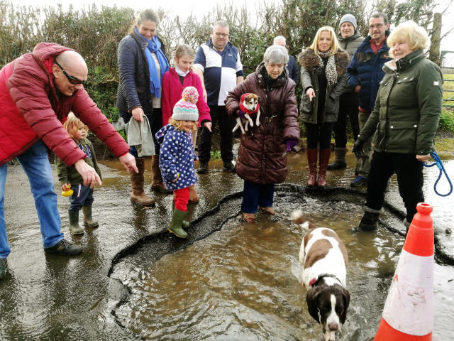 The town councillors and friends in and around the giant pothole in Buckfastleigh, Devon (SWNS)