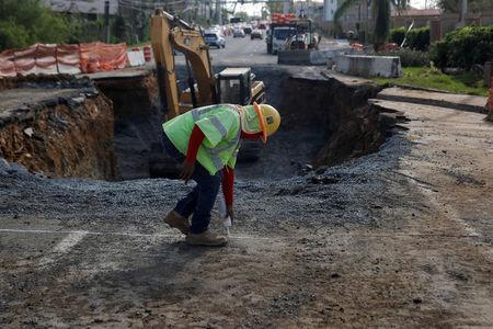 A construction worker sprays paint outside a sinkhole caused by Hurricane Maria at a construction site along Puerto Rico Highway 2, outside San Juan, Puerto Rico, October 12, 2017.  REUTERS/Shannon Stapleton