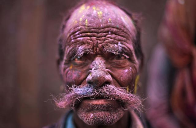 A Hindu devotee, face smeared with colored powder, leaves the Banke Bihari temple during Holi celebrations in Vrindavan, India, Wednesday, March 27, 2013. Holi, the Hindu festival of colors that also marks the advent of spring, is being celebrated across the country Wednesday. (AP Photo/Altaf Qadri)