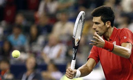 Novak Djokovic of Serbia returns a shot during his men's singles tennis match against Gael Monfils of France at the Shanghai Masters tennis tournament in Shanghai October 11, 2013. REUTERS/Aly Song