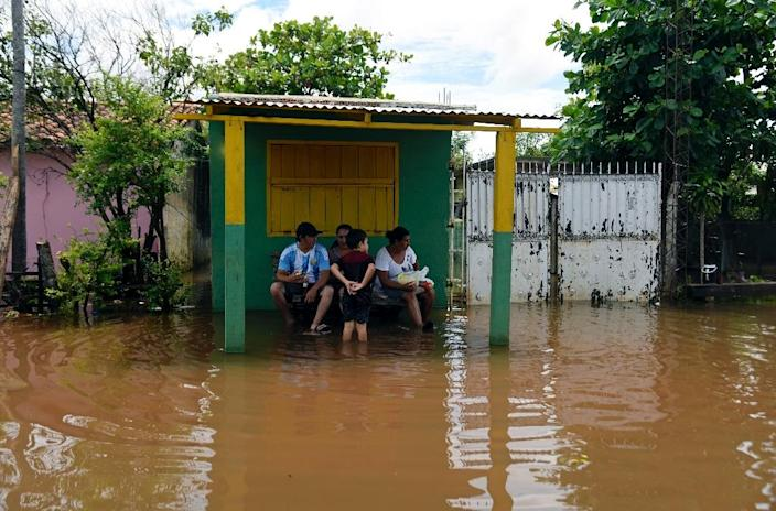 People sit outside their house in a flooded area of Falcon, on the Paraguay-Argentina border on December 26, 2015 (AFP Photo/Norberto Duarte)