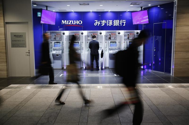 A man uses an ATM machine of Mizuho Bank as pedestrians walk past at a train station in Tokyo