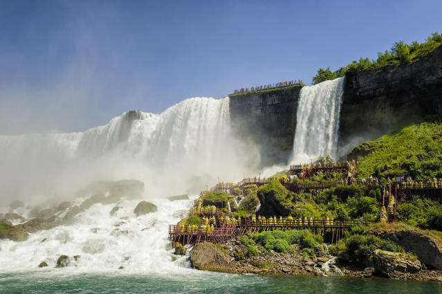 <p>Tourists take the Cave of the Winds tour near the base of the American Falls, one of the three falls that make up Niagara Falls in N.Y. (Photo: Vincent Boisvert/Moment RF/Getty Images) </p>
