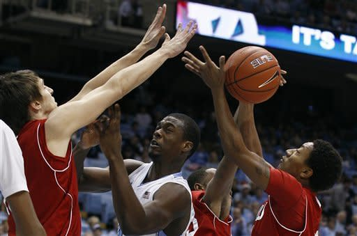 North Carolina's Harrison Barnes, center, struggles for a rebound against Nicholls State's Sam McBeath, left, Trevon Lewis and Shane Rillieux, right, during the first half of an NCAA college basketball game in Chapel Hill, N.C., Monday, Dec. 19, 2011. (AP Photo/Gerry Broome)