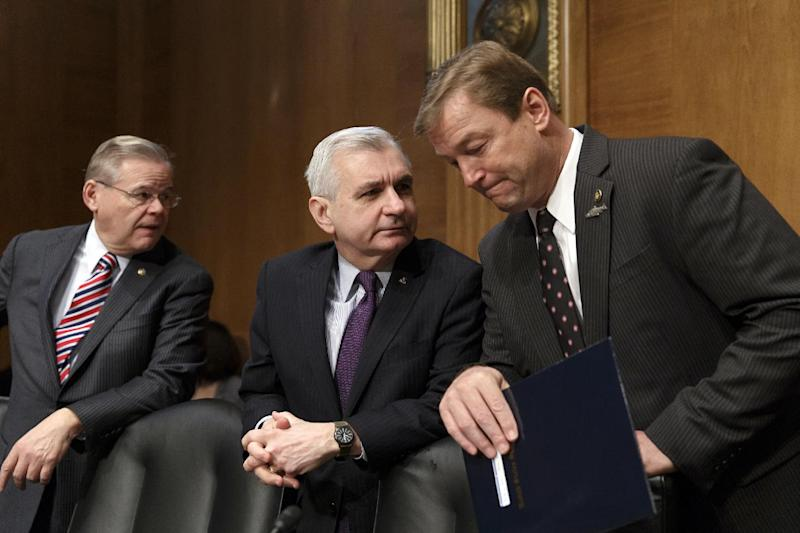 """In this Feb. 27, 2014, file photo, Sen. Jack Reed, D-R.I., center, confers with Sen. Dean Heller, R-Nev., right, with Sen. Robert Menendez, D-N.J., at far left, as members of the Senate Banking Committee gather for an appearance by Janet Yellen on Capitol Hill in Washington. One partisan election-year battle that senators seem likely to resolve when they return from recess later this month is the fight over renewing expired benefits for the long-term unemployed. Reed, a leading bargainer, said the March 13 agreement would help families and """"provide a little certainty to families, business and the markets that Congress is capable of coming together to do the right thing."""" (AP Photo/J. Scott Applewhite, File)"""