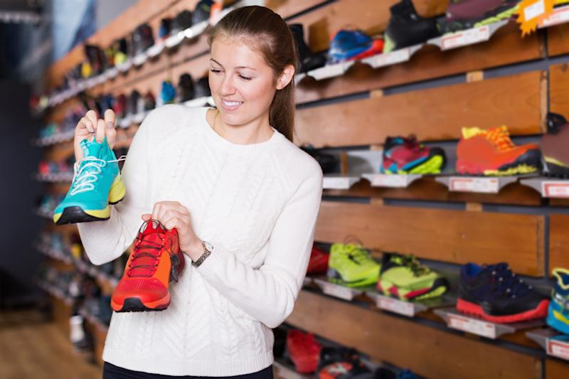 A young woman holding up two different sneakers while shopping in a shoe store.