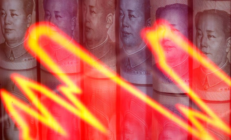 FILE PHOTO: Chinese Yuan banknotes are seen behind illuminated stock graph in this illustration