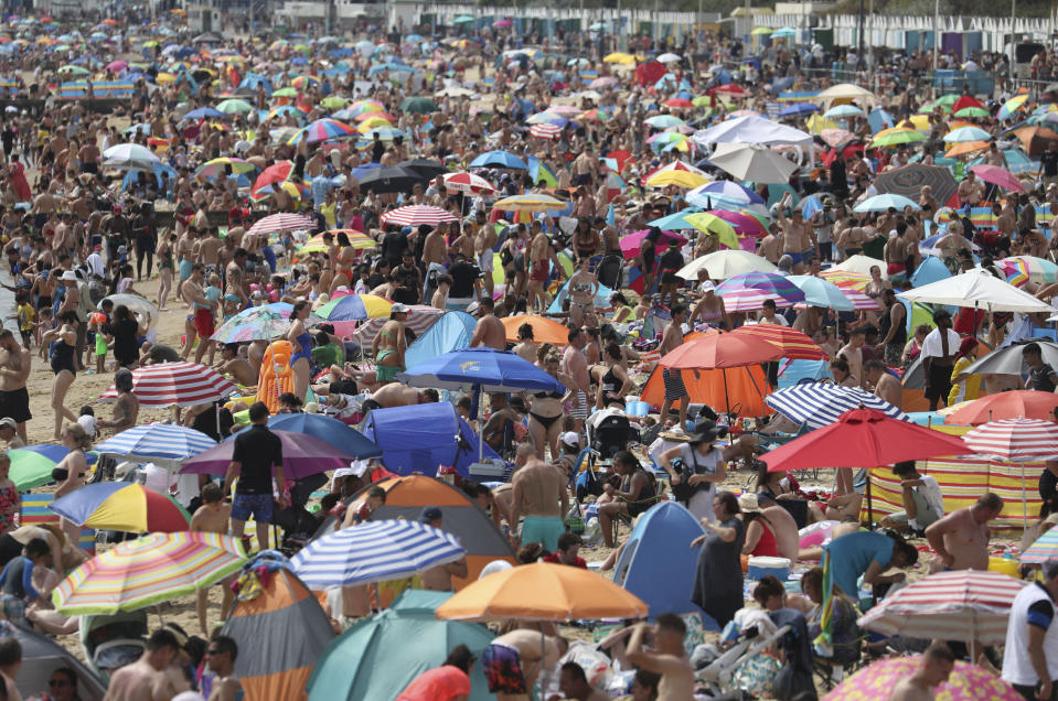People enjoy the hot weather on Bournemouth beach, England, Saturday Aug. 8, 2020. Parts of the UK could see record-breaking overnight temperatures this weekend as the mini heatwave continues. (Andrew Matthews/PA via AP)