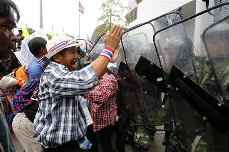 A farmer gestures in front of soldiers guarding the temporary office of Thai Prime Minister Yingluck Shinawatra during a protest in Bangkok February 17, 2014. REUTERS/Chaiwat Subprasom
